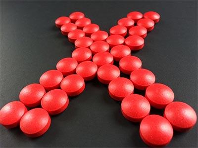Pastillas rojas que forman una x, como indicando que fuera las pastillas