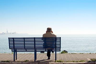 Hombre mayor en un banco que ve pasar la vida en soledad